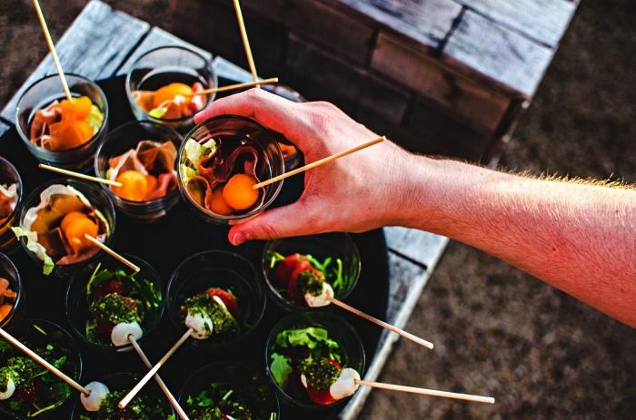recettes faciles et rapides pour un aperitif dinatoire, des brochettes apéritives présentées sur un plateau, des brochettes apéro de mozzarella et tomates et une autre variante avec melon et prosciutto