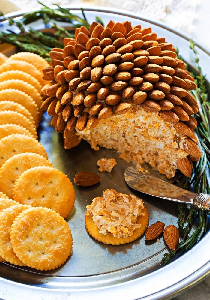 recette de boule au fromage et amandes pour un aperitif noel facile et rapide, plateau avec crackers et boule au fromage façon pomme de pin