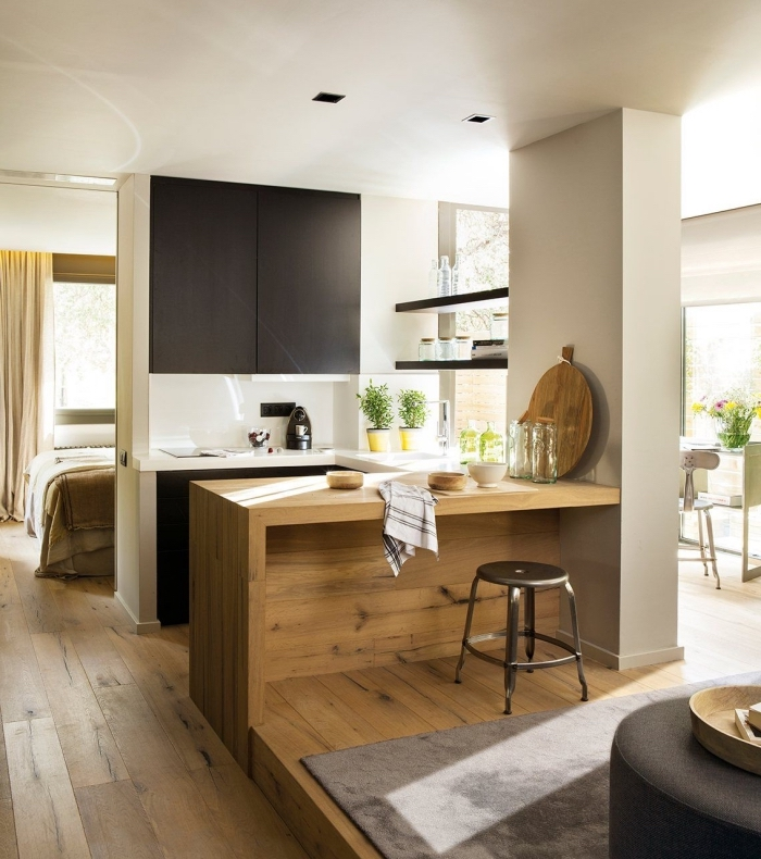 modèle de petite cuisine ouverte avec îlot bar en bois, déco de cuisine blanche avec armoires noir mate et bar en bois