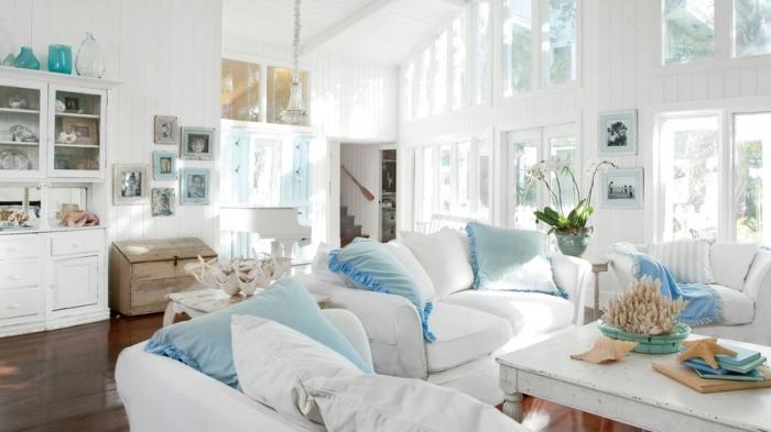 idée déco bord de mer dans un salon blanc à plafond haut avec plancher bois foncé, modèle de coussin bleu turquoise