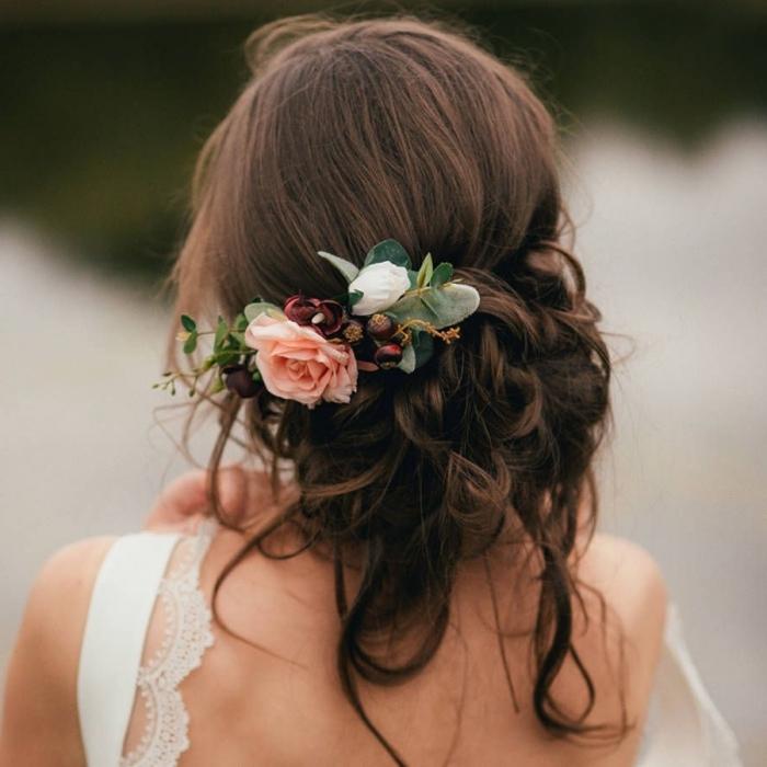 chignon mariee bas et flou avec boucles et accessoire fleuri, idée coiffure mariage pour cheveux longs attachés