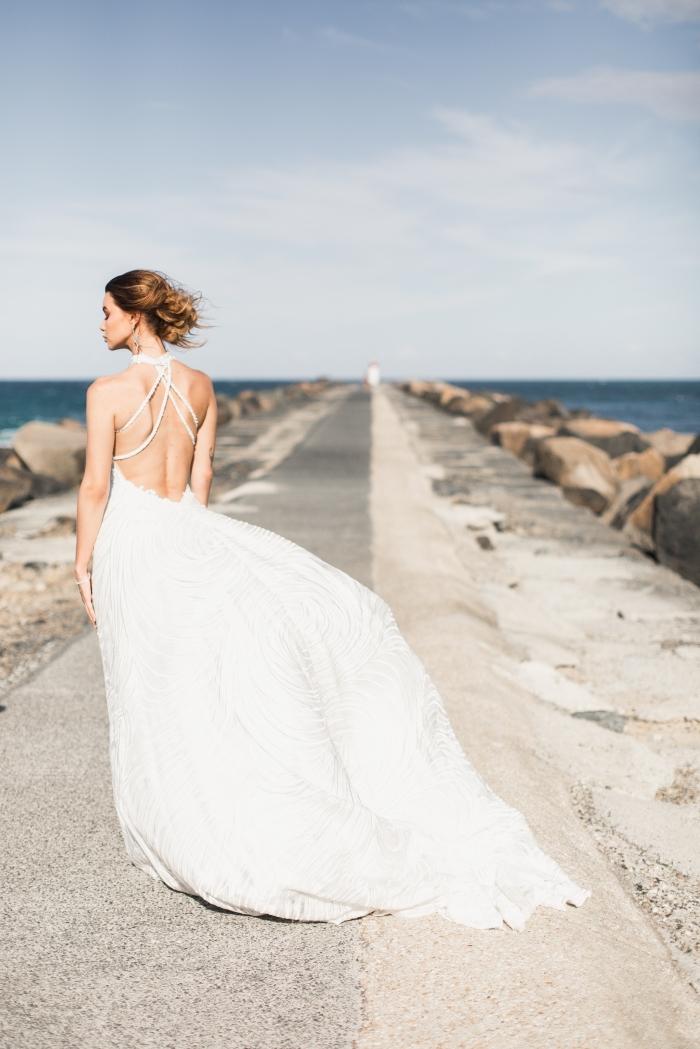 chignon cheveux long pour mariage, idée chignon bas flou sur cheveux longs, modèle robe de mariée longue à dos nu