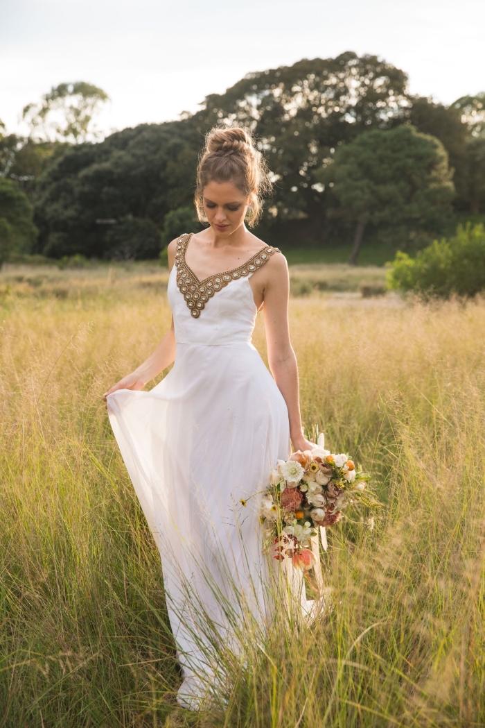 modèle de chignon mariage haut, exemple de robe de mariée longue avec décoration décolleté en or, coiffure cheveux attachés