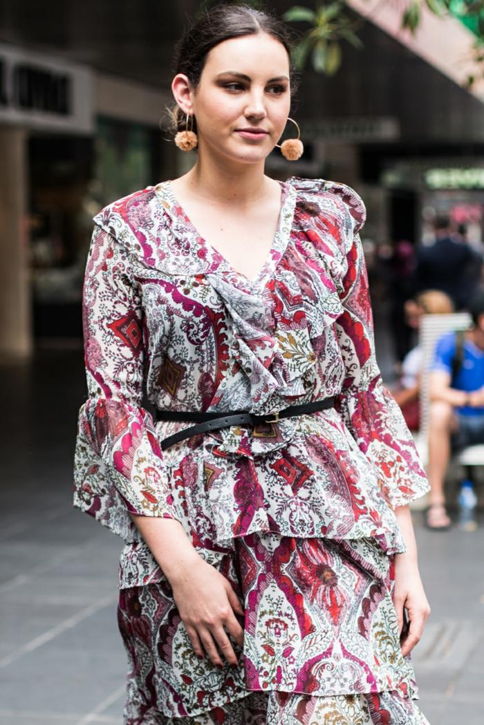 robe gris clair aux motifs rouges, créoles avec grands pompons beiges, chignon, ceinture en cuir