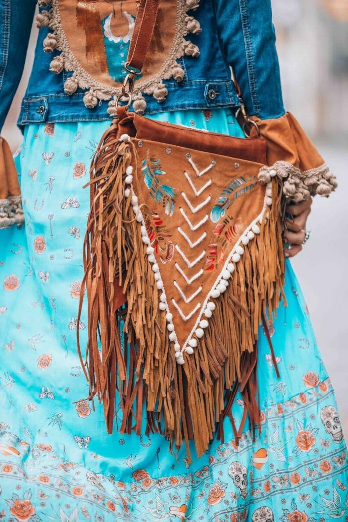 association de sac marron à une jupe bleue aux fleurs rouges, sac avec franges, veste denim avec dos mandala