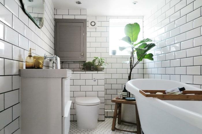 salle de bain look total blanc, grande plante verte, baignoire blanche, miroir sans cadre, tabouret en bois brut