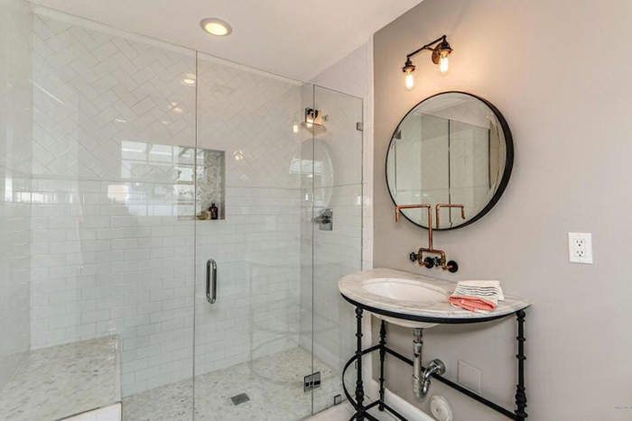 petite salle de bain en noir et blanc, miroir rond, vasque blanche, parois de douche en verre, carrelage douche metro