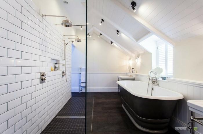 carrelage metro blanc dans une salle de bain en noir et blanc, baignoire rétro, rangement mural intégré