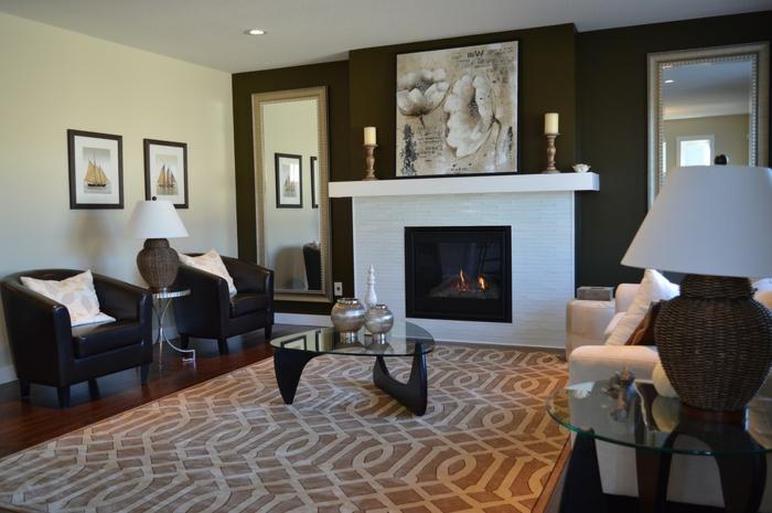 salon compacte et élégant avec cheminée blanche, tapis beige, fauteuils noirs en cuir, table basse