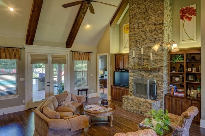 parement pierre pour cheminée, sofa beige, plafond en pente avec poutres en bois, bibliothèque intégrée