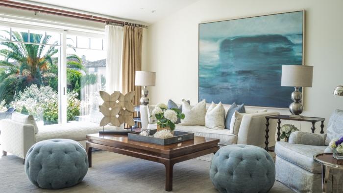 design intérieur salon stylé aux murs blancs avec meubles en bois foncé, art mural avec une peinture océanique pour deco marine
