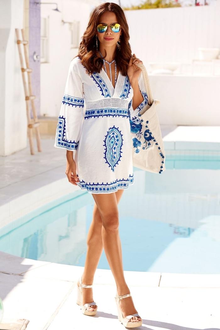 modèle de robe courte blanche avec manches longues à décoration broderie bleu, exemple lunettes de soleil femme