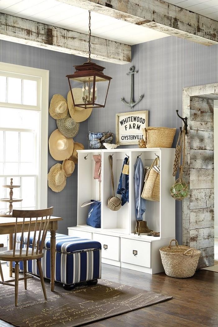 aménagement salon aux murs en papier peint rayures gris et blanc avec plancher foncé, objets en bois pour une couleur bleu marine
