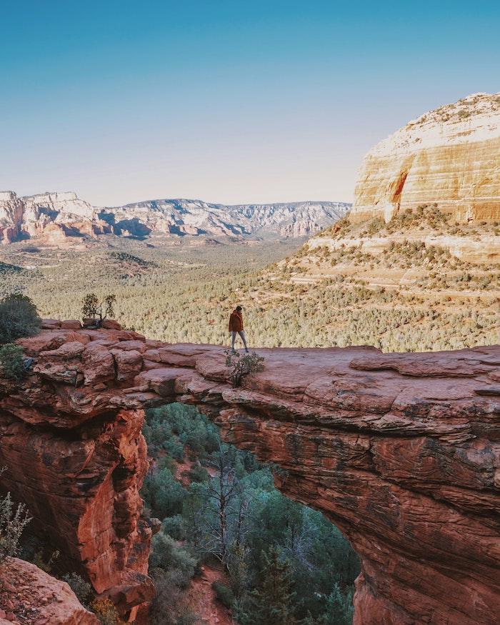 Homme sur pont naturel de rochers dans le parc national d'arisona les plus beaux paysages du monde, belle photo de la terre nature