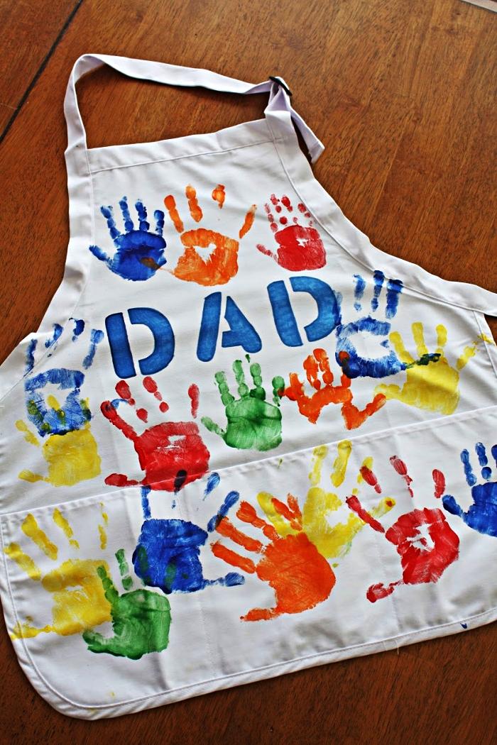 tablier blanc personnalisé avec des empreintes de mains en peinture de couleurs différentes, idéal comme cadeau pour la fête des pères, cadeau fete des peres original pour les plus petits