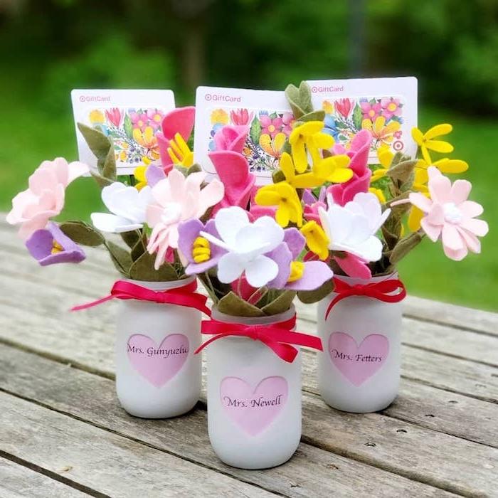 vase de fleurs en pot de verre recyclé repeint en blanc avec coeur rose et nom maitresse écrit dessus et des fleurs en feutrine, étiquette cadeau à motif fleurs