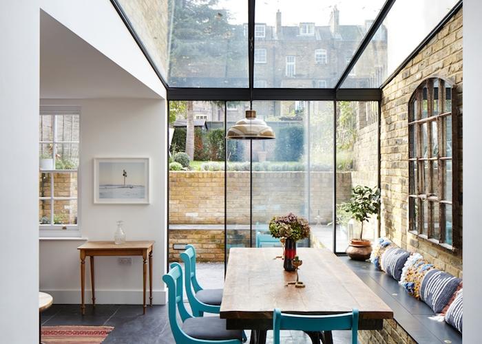 idée salle à manger contemporaine en table et banc de briques et bois avec coussins décoratifs et chaises gris et bleu, ouvertures et fenetre de toit vitrée