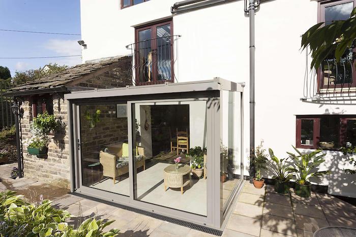 petit salon avec canapé et table de jardin installé sur une véranda vitrée à coté d une maison entourée de verdure
