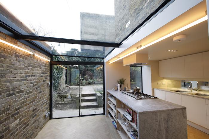 amenagement extension de maison en cuisine blanche avec ilot central marbre gris, parquet clair, verriere exterieure et éclairage LED