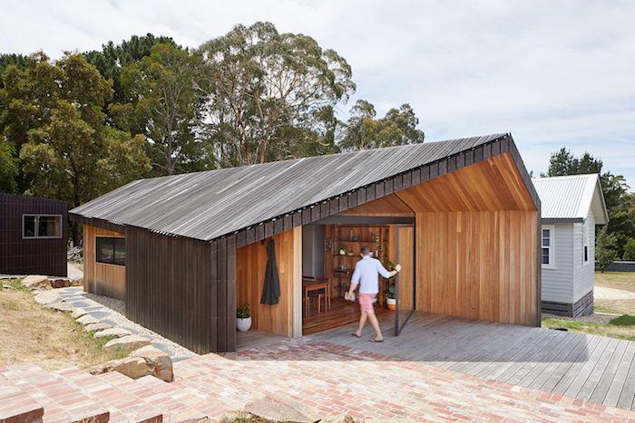 grande extension bois originale style cottage avec une toiture en forme interessante sur une terrasse en bois