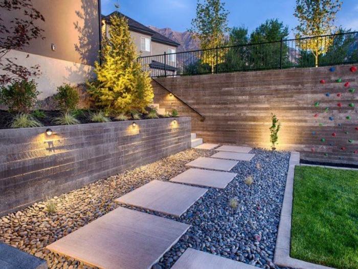 aménagement- paysager, allée dalles, gravier décoratif, pelouse verte, lampes fixées à un muret, parterre surélevé