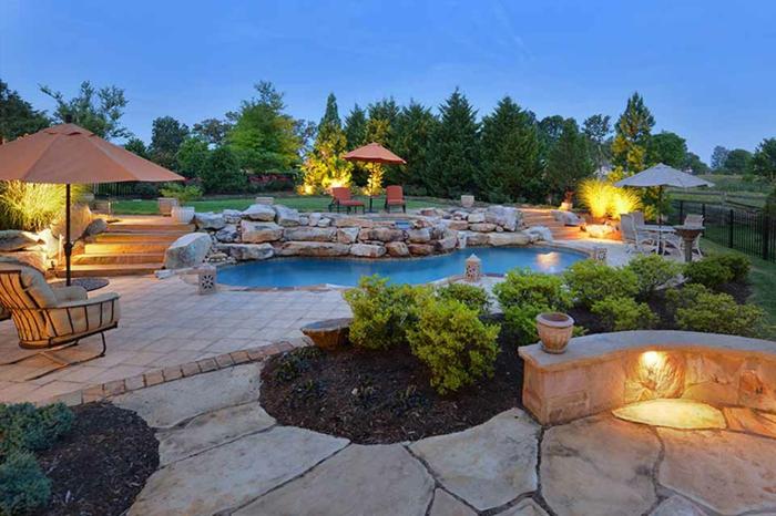 aménagement jardin paysager, dalles de pierre, piscine, pelouse, joli éclairage, plusieurs abris de jardin