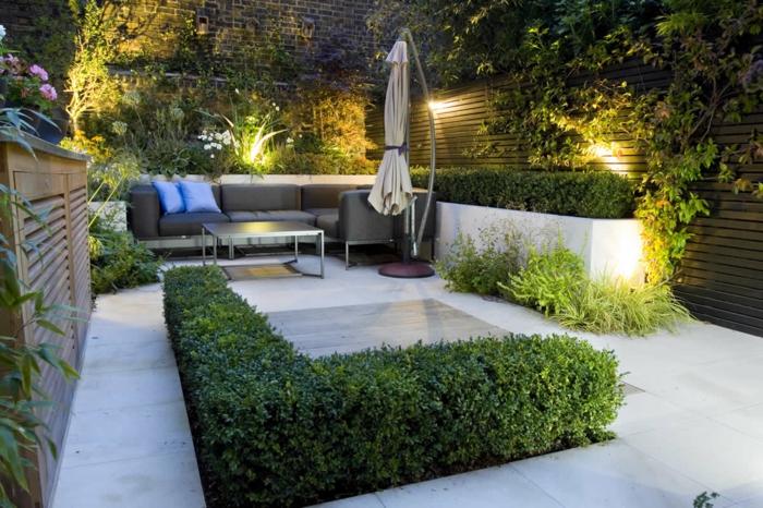 creation jardin paysager, haie tondue, dalles en béton, parasol de jardin, sofa gris, cloison bois éclairée