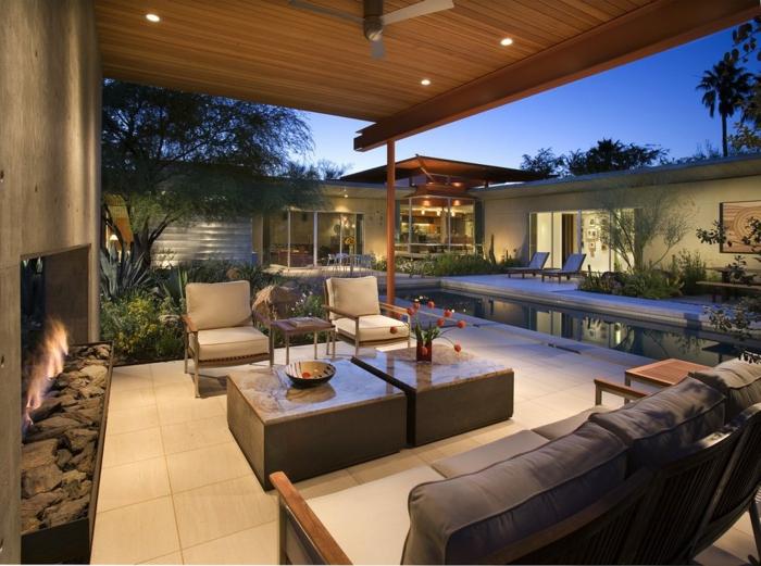decoration jardin moderne, foyer extérieur, tables basses, modernes, longue piscine, chaises blanches, tonnelle en bois, aménagement extérieur maison, joli espace paysager