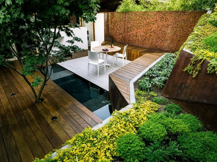 aménagement extérieur originale, terrasses en bois, parterres de plantes vertes, piscine enterrée et terrasse avec petite table