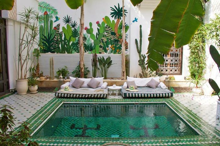 aménagement paysager oriental, piscine carrée, dessins muraux de cactées géantes, sofas matelas, carreaux de ciment
