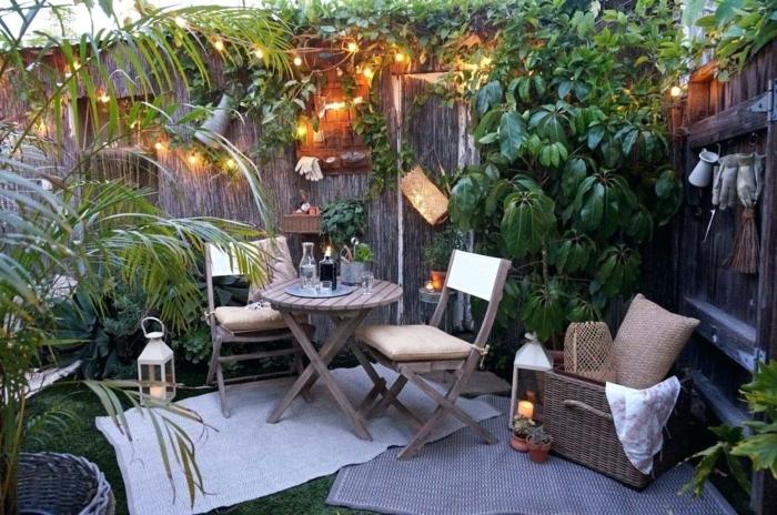 jardin paysager, table et chaises, panier rustique, coussin en jute, lanternes grecques, guirlande lumineuse, salon de jardin coquet
