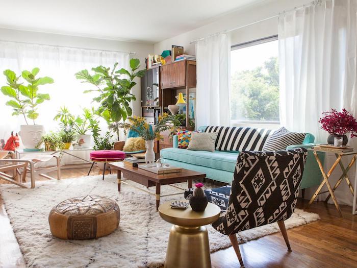 deco jungle dans le salon, tapis blanc moelleux, canapé bleu, coussins zèbre, pouf oriental par son, mobilier bois, table laiton, plantes en pot sur table de service