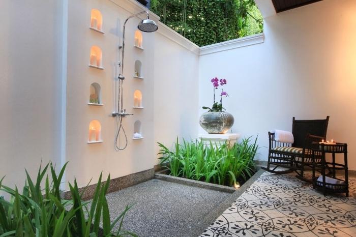 modèle de salle de bain zen dans le jardin avec douche pluie en inox et meubles de jardin en bois tressé noir