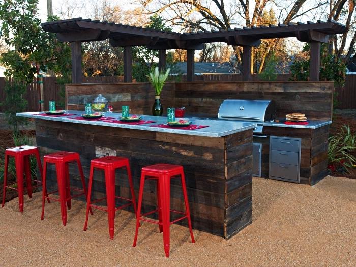 cuisine extérieure avec plancha, ilot central palette et tabourets de bar de style industriel, aménager une cuisine extérieure avec des palettes