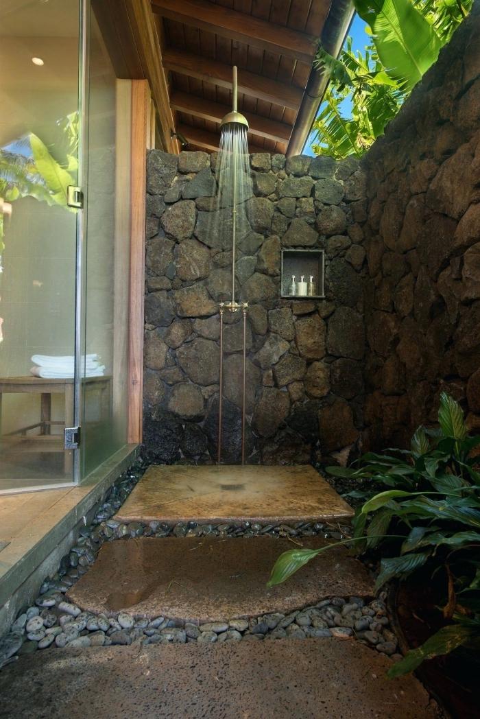 modèle de petite salle de bain zen aménagée dans le jardin avec murs en pierre et receveur de douche en pierre