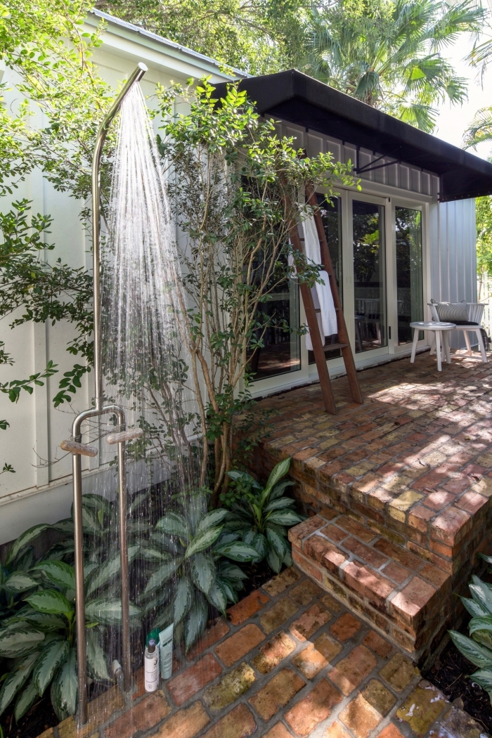 décoration de jardin avec revêtement de sol en briques et douche fixe en métal, idée aménagement terrasse en briques