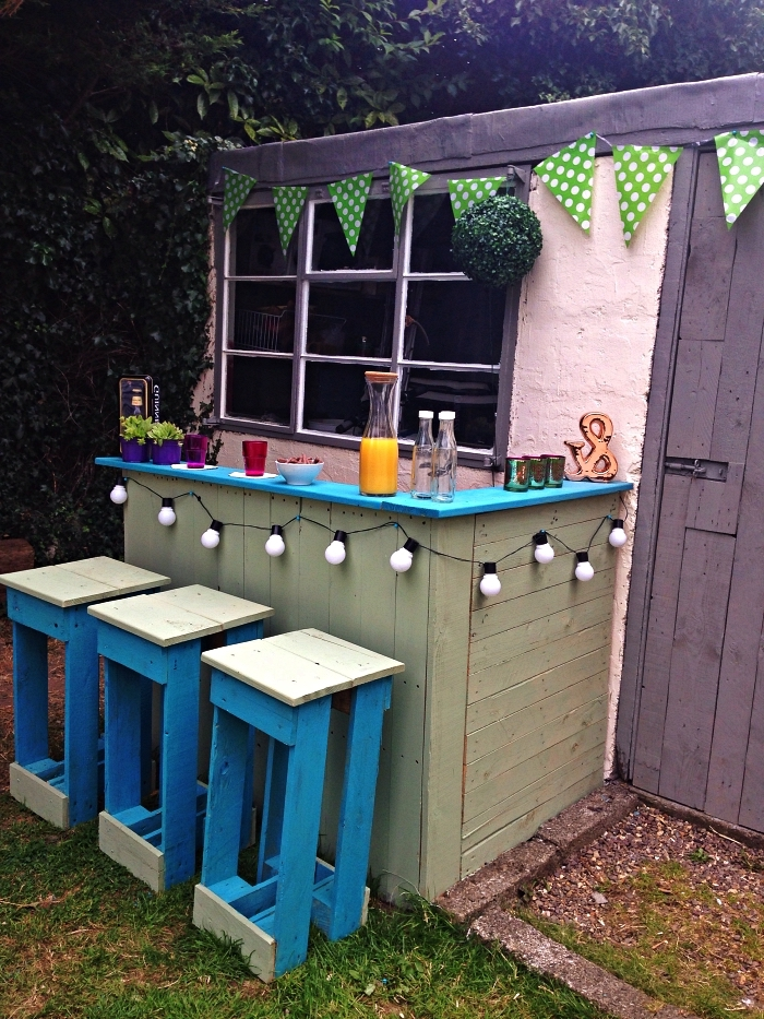 deco bar de jardin guinguette en palettes avec guirlandes à lampes et fanions, aménagement d'un coin bar dans le jardin