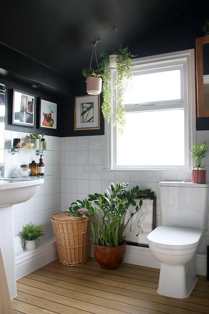 idée déco bohème chic dans une petite salle de bain blanc et noir au sol bois, idée plantes vertes d'intérieur et accessoires bois