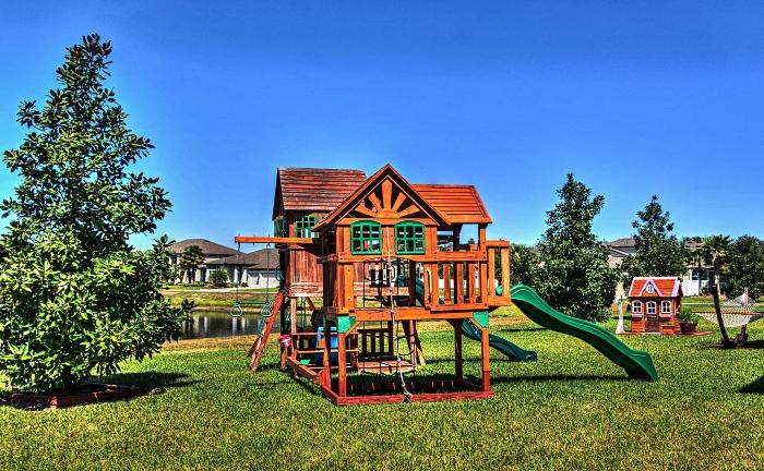espace de jeu avec maisonnette en bois qui combinée deux toboggans, un filet et des anneaux