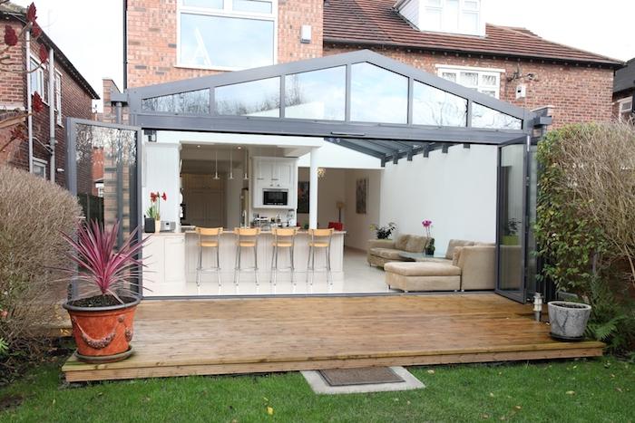 modele de cuisine blanche avec bar à chaises de bois et métal à coté d un coin salon avec canapé gris, murs blancs, terrasse de bois
