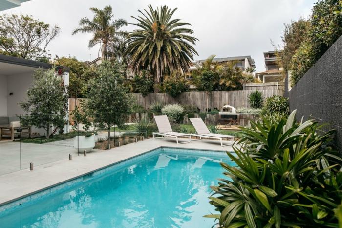piscine moderne, chaises-longues blanches, palmiers, terrasse en dalles blanches, espace paysager contemporain