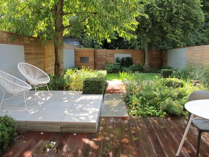 jardin paysager bois et blanc, chaises papasan blanches, dalles en marbre blanc, terrasse planches de bois, gazon tondu, arbustes