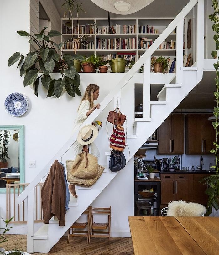 urban jungle deco salon, bibliothèque blanche avec coin de lecture sur mezzanine, escalier blanc, avec cuisine bois en dessous, table salle à manger bois
