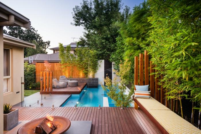amenagement jardin paysager, terrasse en bois, foyer extérieur, cloison en bois, piscine enterrée