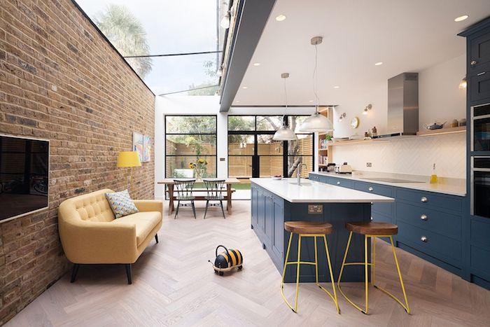 petit studio extension de maison avec cuisine en bleu de gris et ilot central bleu, tabourets de bar, canapé jaune et coin repas en table bois et chaises de metal, parquet bois clair, toiture partiellement vitrée