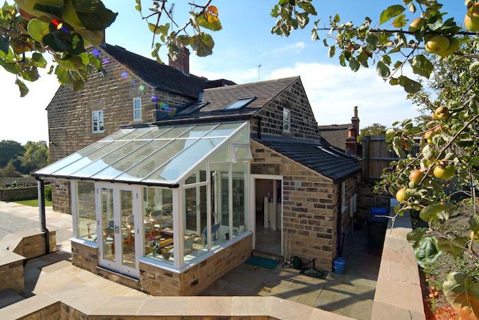 veranda victorienne comme extension d une maison traditionnelle de briques avec coin repos en chaises et table, baies, toiture vitrées