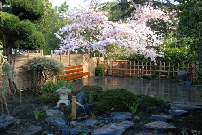 jardin zen, banquette, pierres décoratives, lanterne japonaise, clôture bambou, arbre fleuri