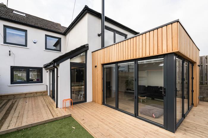 agrandissement maison bois avec à baies vitrées avec canapé noir et table basse, installation extension sur terrasse exterieure de teck