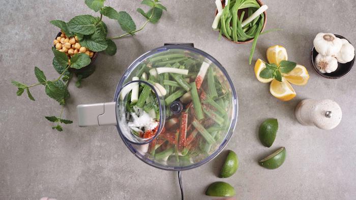 assaisonner le persil, les oignons verts et les pois chiches pour faire une recette falafel en apero dinatoire light