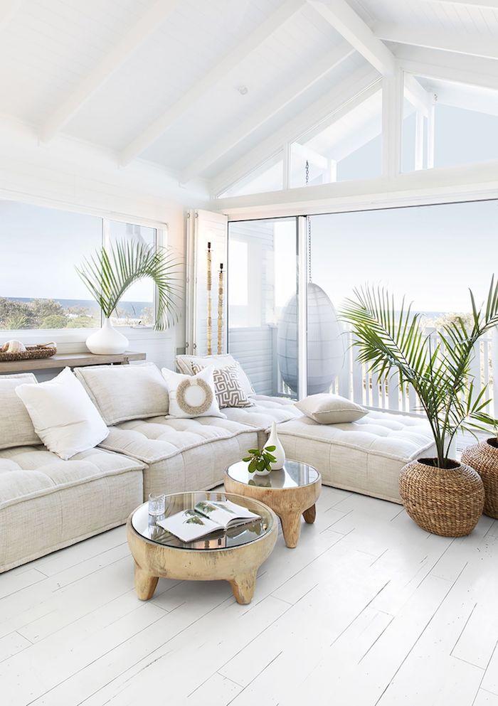 Grand salon avec fenetres ouvertes, table basse bois salon, canapé blanc coussin boheme, déco berbère, aménagement chambre